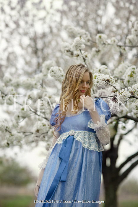 Nikaa BLONDE WOMAN IN BLUE BY TREE IN BLOSSOM