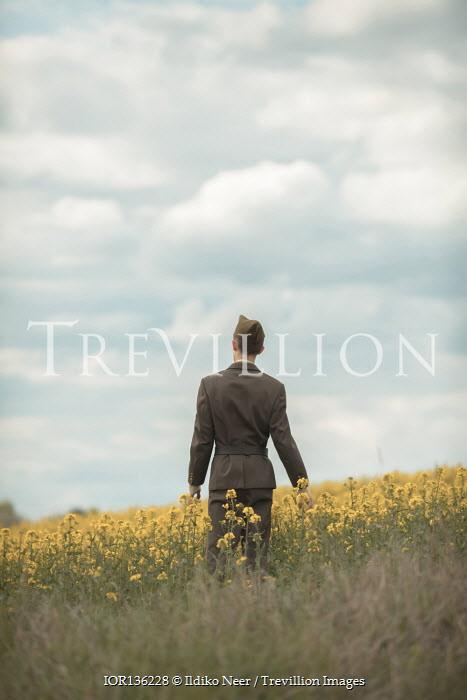 Ildiko Neer soldier walking in meadow of yellow flowers