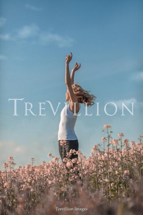 Ildiko Neer Young woman jump up in meadow