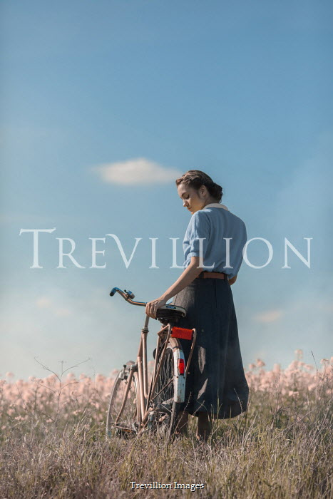 Ildiko Neer Vintage woman standing with bicycle in meadow