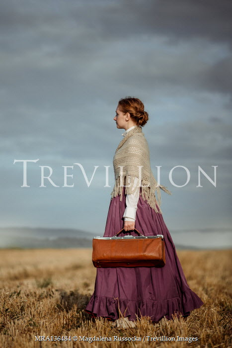 Magdalena Russocka historical woman carrying bag standing in field