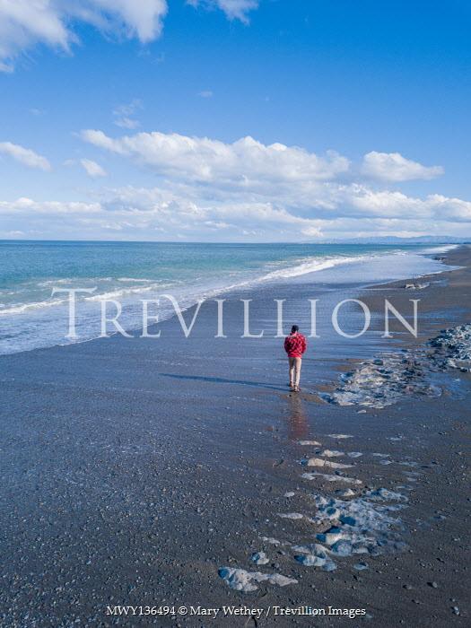 Mary Wethey MAN WALKING ON BEACH WITH BLUE SKY