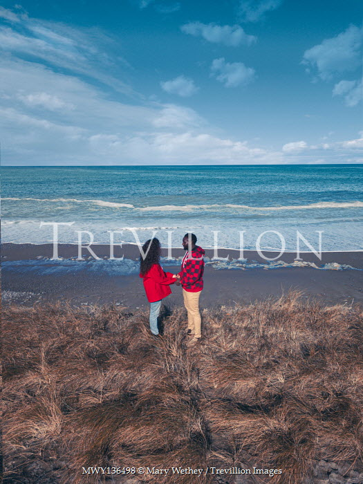 Mary Wethey COUPLE STANDING HOLDING HANDS ON BEACH