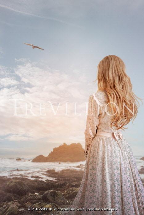 Victoria Davies BLONDE WOMAN IN DRESS ON ROCKS WATCHING SEA