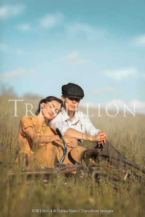 Ildiko Neer Vintage couple sitting in grass with bicycle