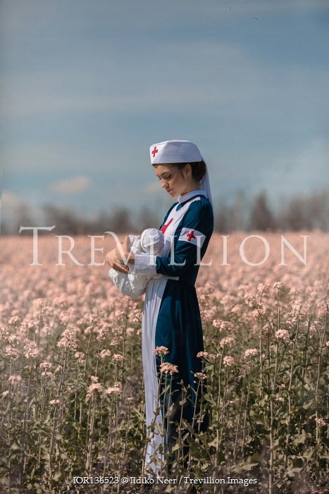 Ildiko Neer Wartime nurse holding baby in meadow