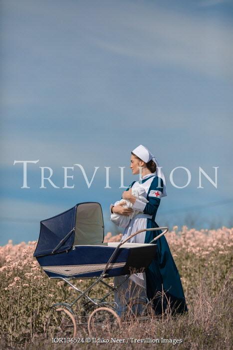 Ildiko Neer nurse holding baby in meadow by pram