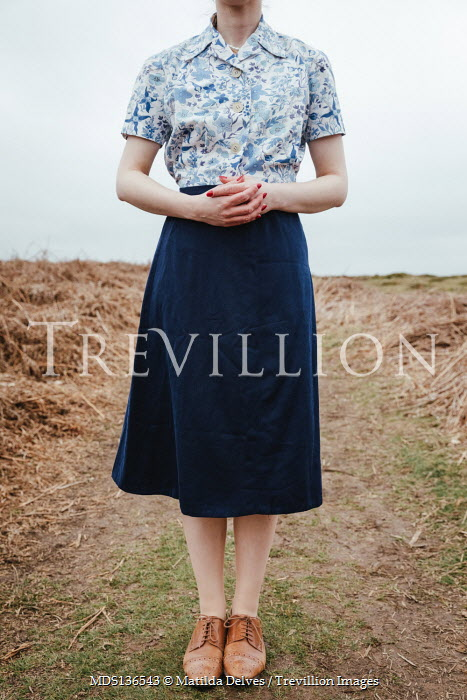 Matilda Delves RETRO WOMAN IN FLORAL BLOUSE STANDING IN COUNTRYSIDE
