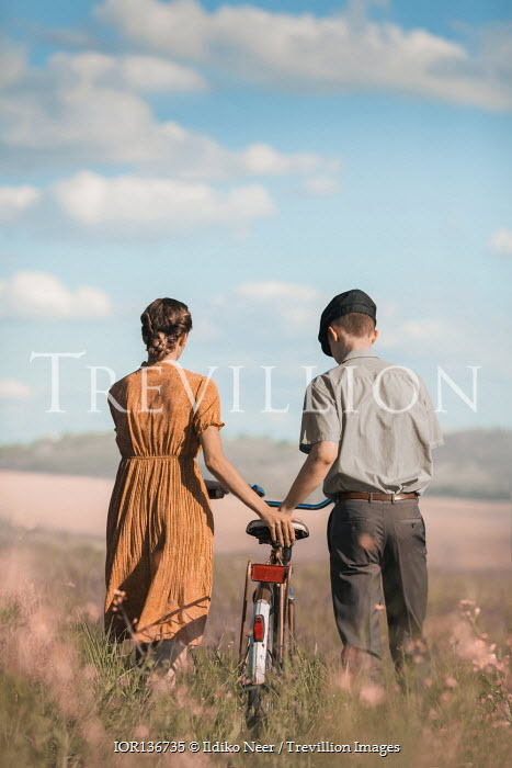 Ildiko Neer Vintage couple with bicycle in meadow