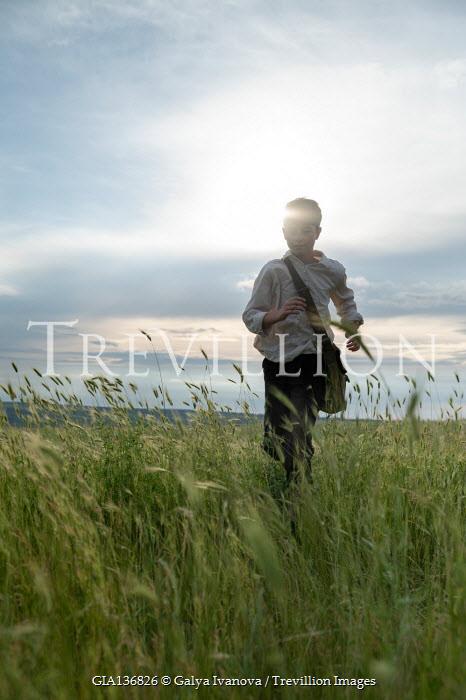 Galya Ivanova BOY WITH BAG RUNNING IN LONG GRASS