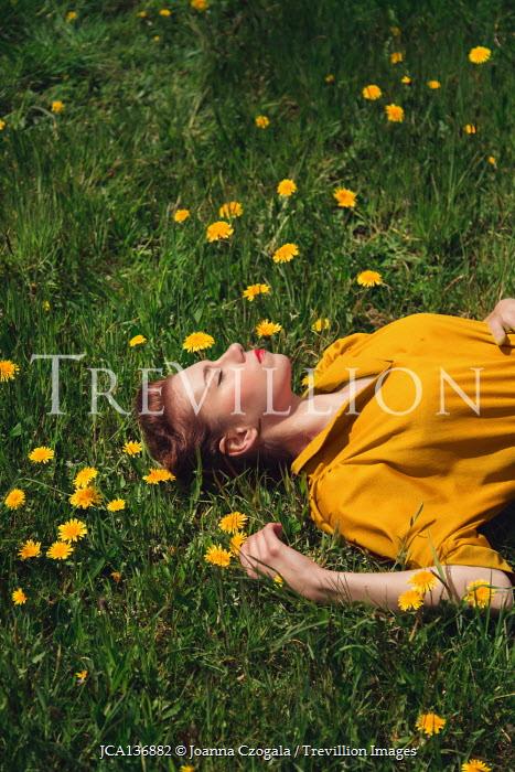 Joanna Czogala WOMAN IN YELLOW DRESS LYING IN FIELD WITH DANDELIONS
