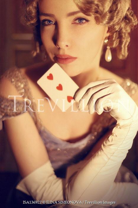 ILINA SIMEONOVA BLONDE REGENCY WOMAN HOLDING PLAYING CARD INDOORS