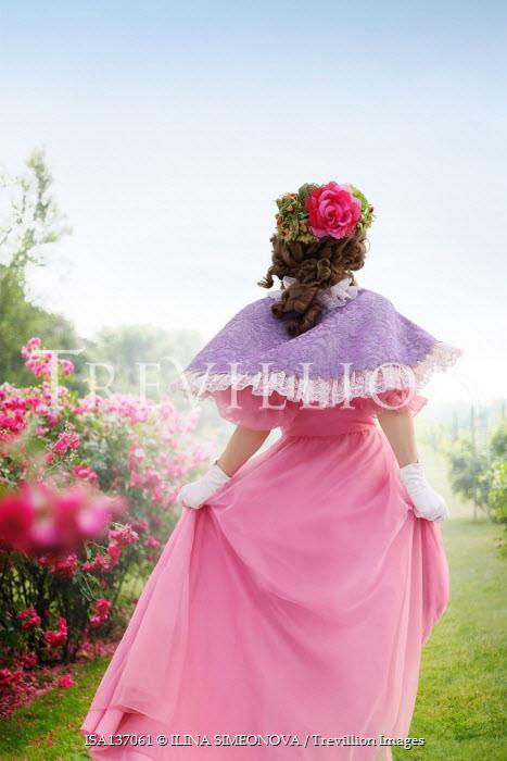 ILINA SIMEONOVA BRUNETTE WOMAN IN PINK WALKING IN SUMMERY GARDEN