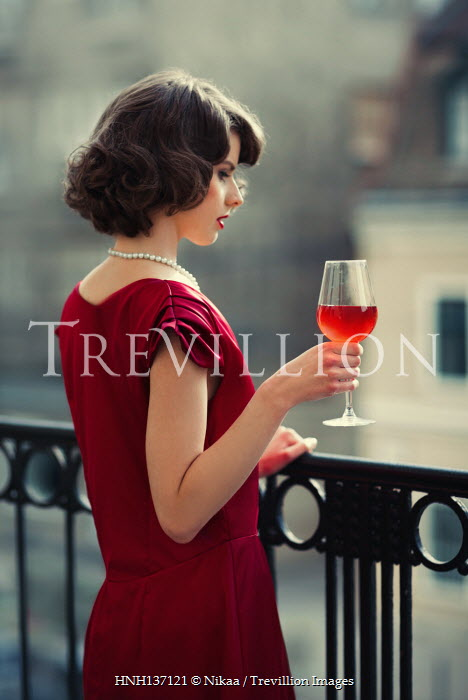 Nikaa WOMAN IN RED ON BALCONY WITH GLASS OF WINE