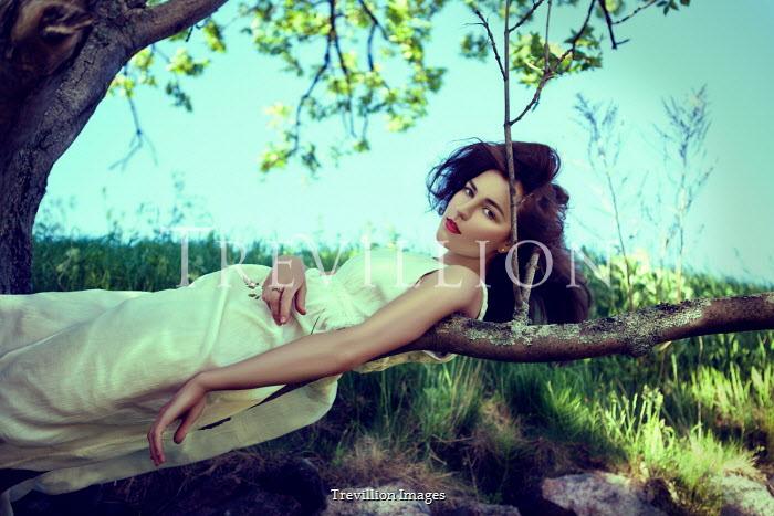 Marina Chebanova BRUNETTE WOMAN IN WHITE LYING ON BRANCH