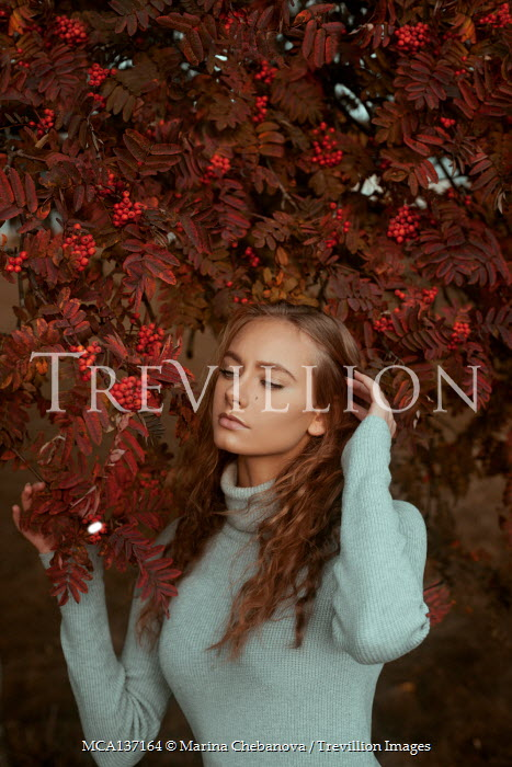 Marina Chebanova BRUNETTE WOMAN STANDING BY TREE WITH RED BERRIES