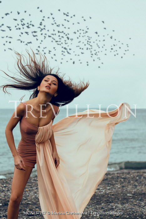 Marina Chebanova BRUNETTE WOMAN ON BEACH WITH FLOWING DRESS