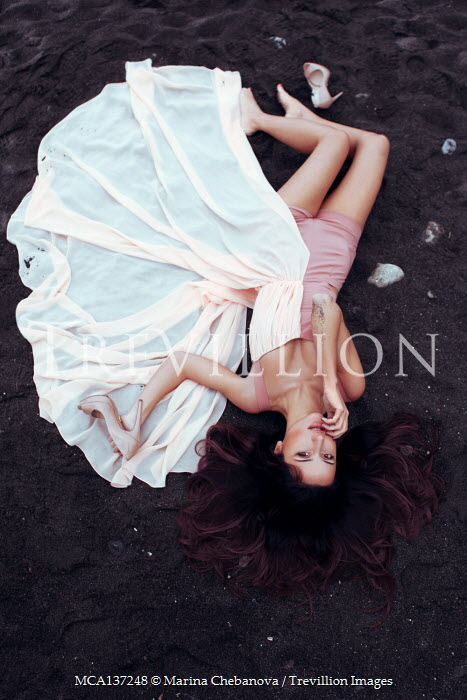 Marina Chebanova WOMAN IN FLOWING DRESS LYING ON BLACK SAND