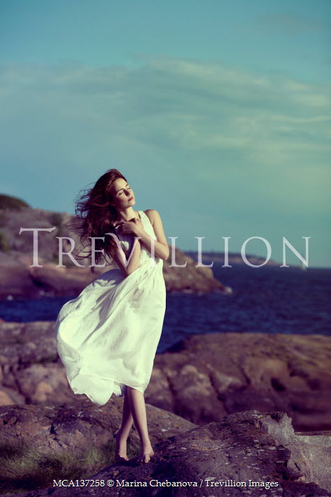 Marina Chebanova WOMAN IN WHITE ON ROCKS BY WINDY SEA