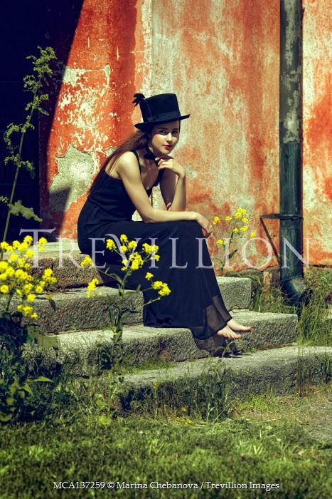 Marina Chebanova WOMAN IN TOP HAT SITTING ON STEPS OUTDOORS