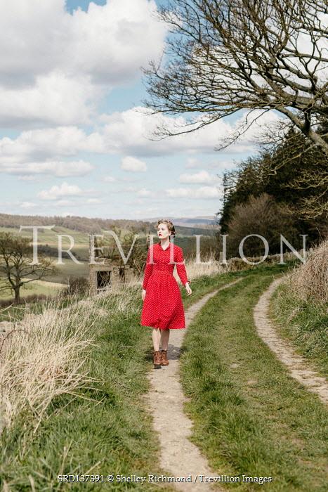 Shelley Richmond WOMAN IN RED DRESS WALKING IN COUNTRYSIDE ROAD
