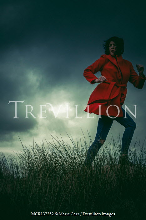 Marie Carr WOMAN IN RED COAT RUNNING ON STORMY DUNES