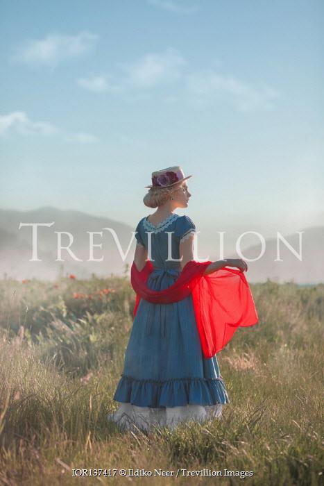 Ildiko Neer Historical woman standing in field by hills