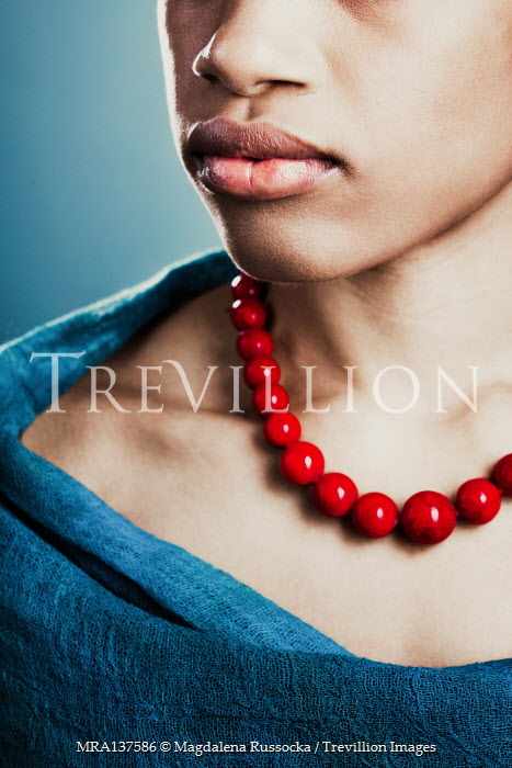 Magdalena Russocka close up of young african woman with red coral necklace wrapped with blue shawl inside