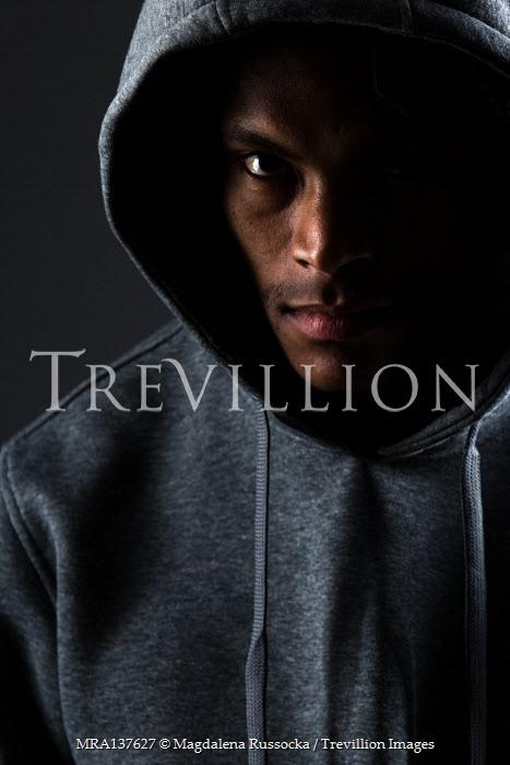 Magdalena Russocka young african man wearing hoodie in shadow inside