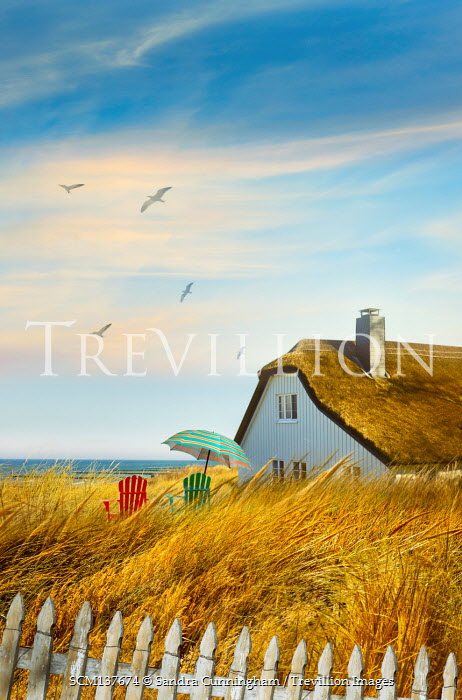 Sandra Cunningham THATCHED HOUSE WITH CHAIRS AND UMBRELLA BY SEA