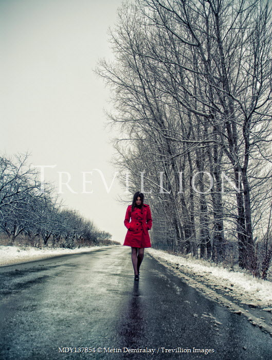 Metin Demiralay WOMAN IN RED COAT WALKING IN WINTRY COUNTRY ROAD