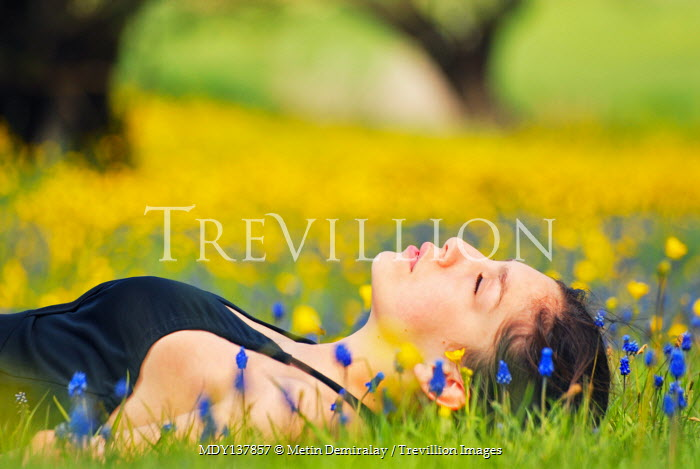 Metin Demiralay DAYDREAMING GIRL LYING IN MEADOW OF FLOWERS