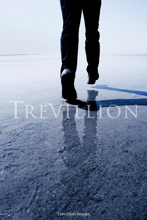 Tim Robinson MAN WALKING ON SANDY BEACH