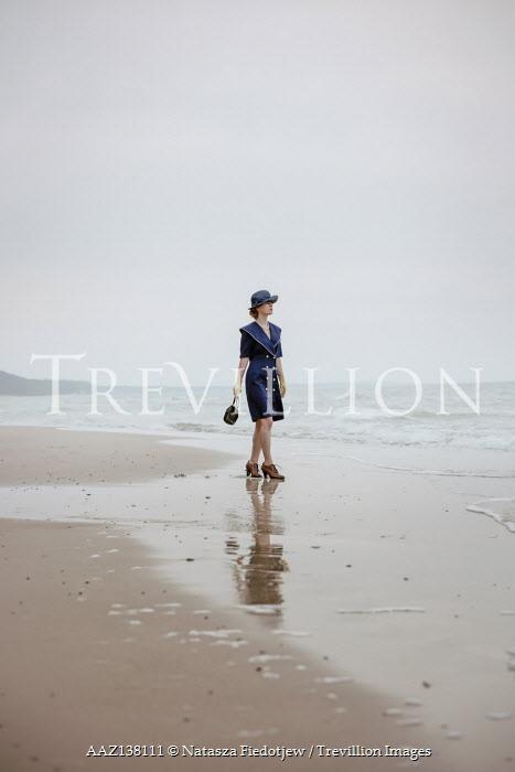 Natasza Fiedotjew Vintage woman in hat holding purse walking on beach by sea