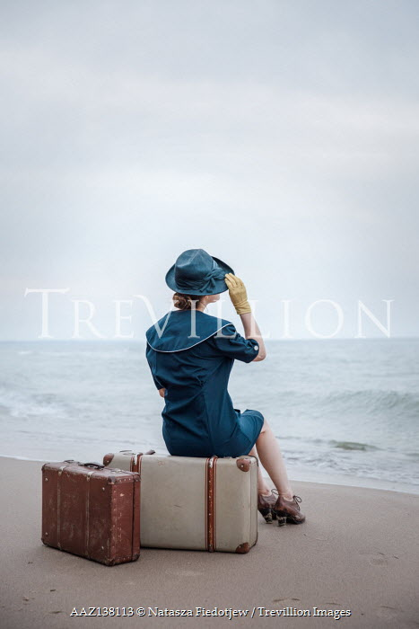 Natasza Fiedotjew Vintage woman on beach by sea sitting on suitcases