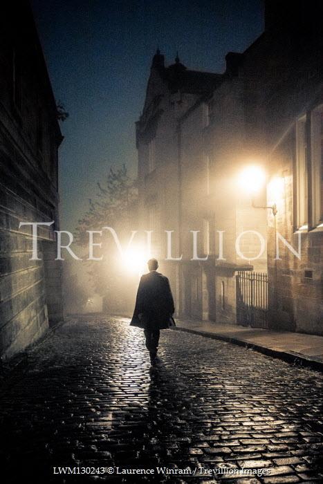 Laurence Winram Man in coat walking on cobblestone street at night