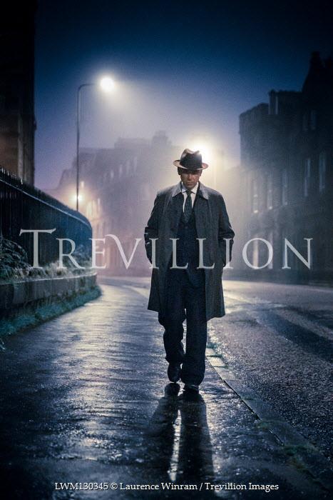 Laurence Winram RETRO MAN WALKING IN CITY STREET AT NIGHT