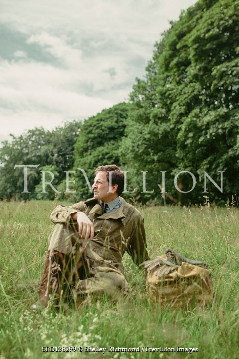 Shelley Richmond MAN SITTING ON GRASS IN FLYING SUIT