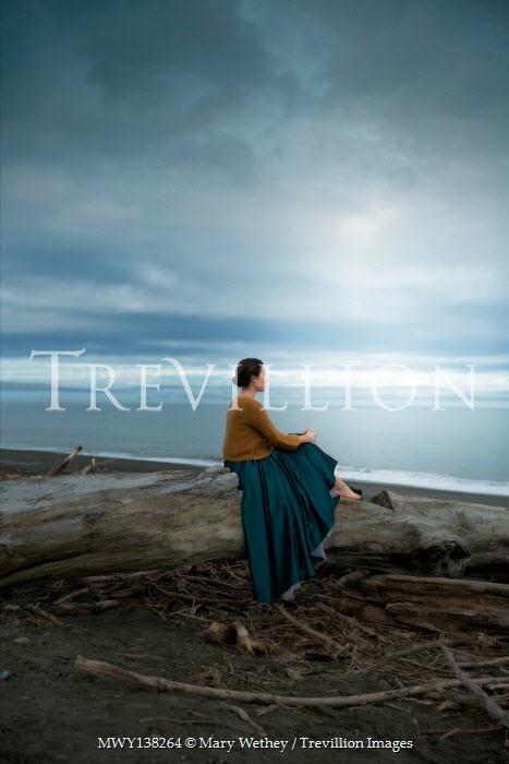 Mary Wethey WOMAN WITH SHAWL SITTING ON LOG BY BEACH