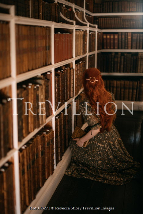 Rebecca Stice WOMAN WITH RED HAIR KNEELING BY BOOK SHELVES