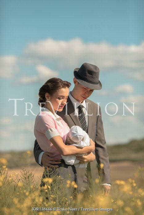 Ildiko Neer Vintage couple holding baby in meadow