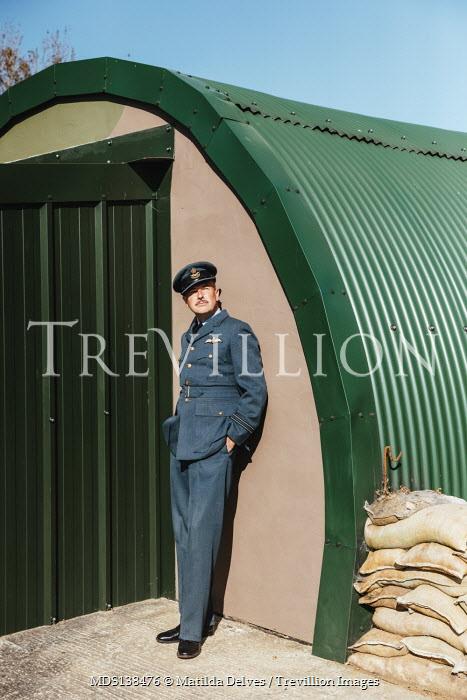 Matilda Delves WARTIME PILOT WAITING OUTSIDE BUILDING WITH SANDBAGS