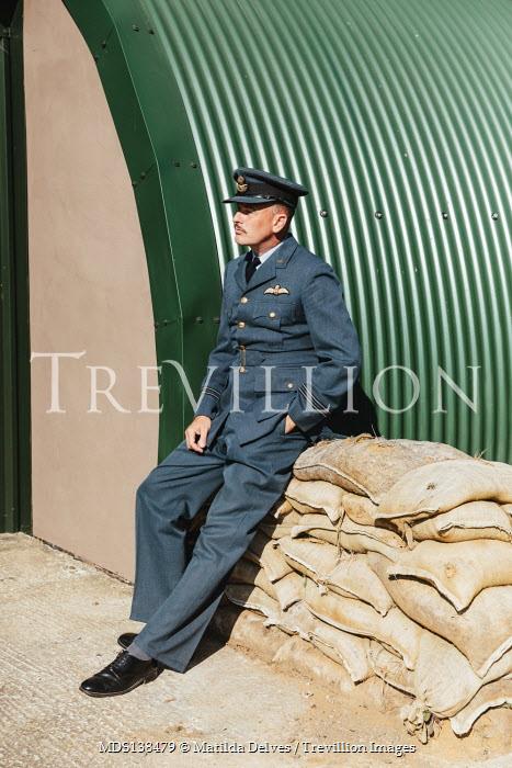 Matilda Delves WARTIME PILOT SITTING ON SANDBAGS OUTSIDE BUILDING