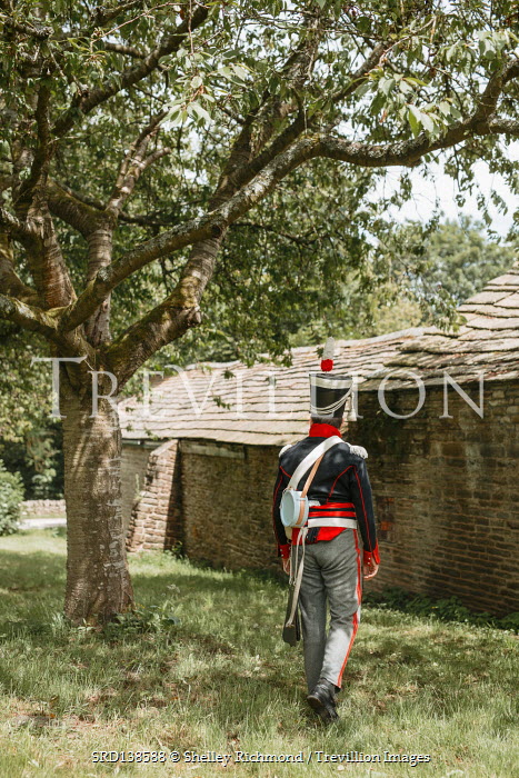 Shelley Richmond HISTORICAL SOLDIER WALKING BY BUILDING IN COUNTRYSIDE