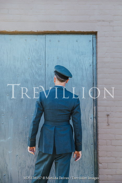 Matilda Delves WARTIME AIRMAN OUTSIDE BY DOORWAY