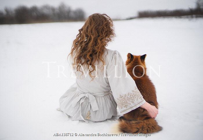Alexandra Bochkareva WOMAN AND FOX SITTING IN SNOWY COUNTRYSIDE