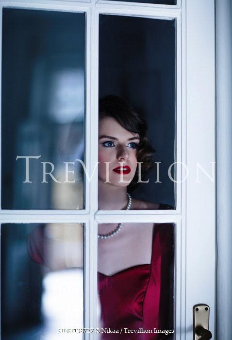 Nikaa RETRO WOMAN BY GLASS DOOR AT NIGHT