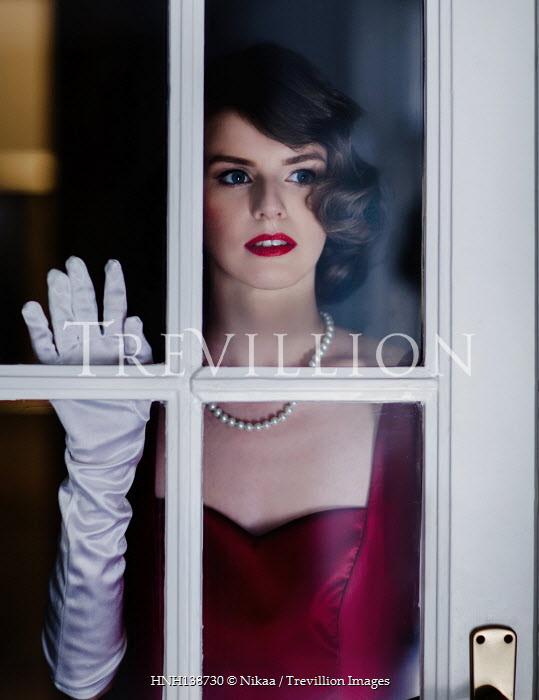 Nikaa RETRO WOMAN TOUCHING GLASS DOOR AT NIGHT