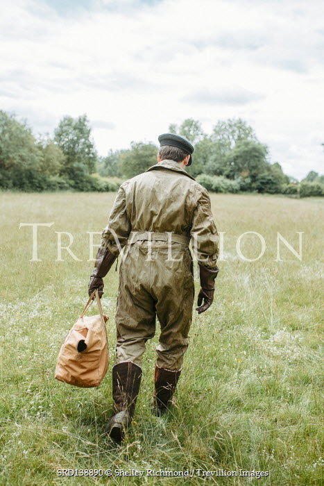 Shelley Richmond MAN WITH FLYING SUIT WALKING IN FIELD