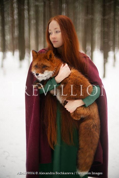 Alexandra Bochkareva WOMAN WITH CAPE HOLDING FOX IN SNOWY FOREST